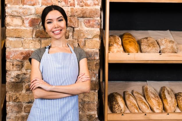 Überzeugter weiblicher bäcker, der nahe dem hölzernen regal mit gebackenen broten steht Kostenlose Fotos