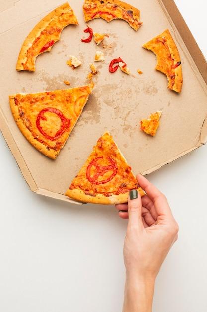 Übrig gebliebene pizza und person, die ein stück nimmt Premium Fotos