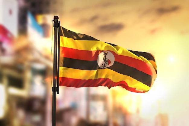Uganda-flagge gegen stadt verschwommen hintergrund bei sonnenaufgang hintergrundbeleuchtung Premium Fotos