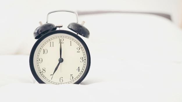 Uhr auf weißem, bequemem bett. Premium Fotos