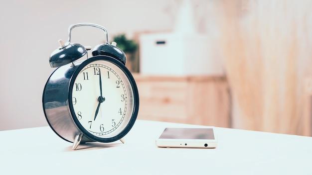 Uhr auf weißer tabelle. Premium Fotos