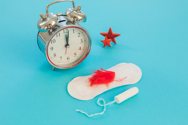 Uhr mit damenbinden und tampon Kostenlose Fotos