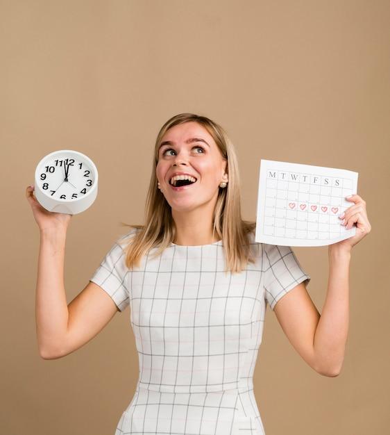 Uhr und periodenkalender von frau gehalten Kostenlose Fotos