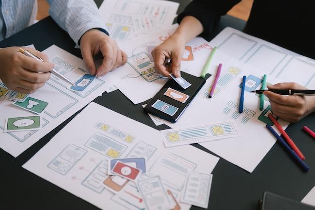 Ui-ux-designer-meeting-web-smartphone-layout-anwendungsprototyp in nahaufnahme Premium Fotos