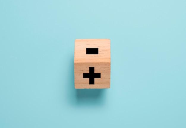 Umdrehen des holzwürfelblocks, um das minuszeichen in ein pluszeichen auf dem blauen tisch zu ändern. positives denken und denkkonzept. Premium Fotos