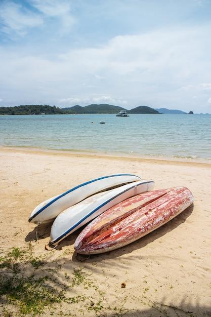 Umgedrehte weiße und rote kajaks halten am strand mit meer und berg mit klarem blauem himmel Premium Fotos