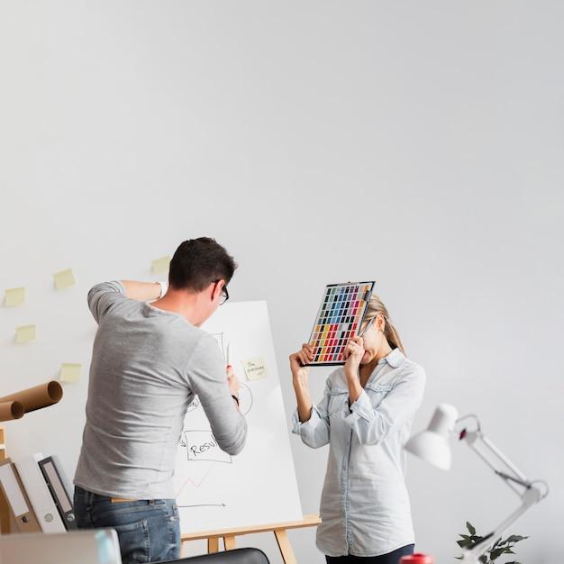 Umgekippte frau und mann, die an unternehmensproblemen arbeiten Kostenlose Fotos