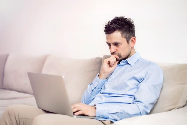 Umgekippter und besorgter junger geschäftsmann, der am laptop sitzt und arbeitet Premium Fotos