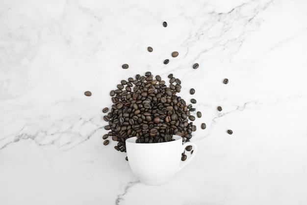 Umgeworfenes weißes glas und kaffeebohnen vereinbarten auf einer marmoroberfläche in der draufsicht. Premium Fotos