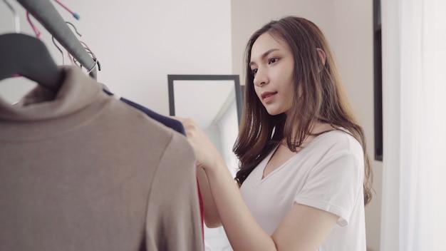 Umkleideraum der hauptgarderobe oder des kleidungsgeschäfts. asiatische junge frau, die ihre modeausstattungskleidung wählt Kostenlose Fotos