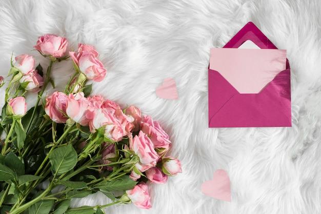 Umschlag in der nähe von frischen blüten auf wolldecke Kostenlose Fotos