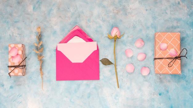 Umschlag in der nähe von geschenkboxen, blumen und blütenblättern Kostenlose Fotos