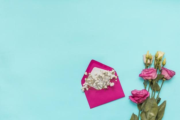 Umschlag mit blumenzweigen und rosen Kostenlose Fotos