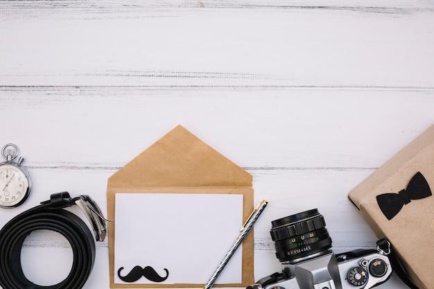 Umschlag mit papier in der nähe von kamera, box, stoppuhr und lederarmband Kostenlose Fotos