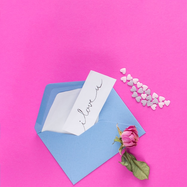 Umschlag mit papier mit titel in der nähe von ornamentherzen und -blumen Kostenlose Fotos
