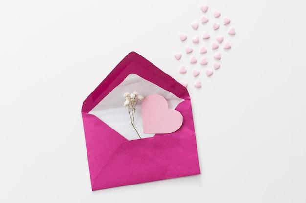 Umschlag mit papierherz und pflanzenzweig Kostenlose Fotos