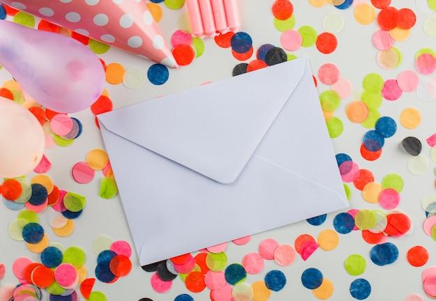 Umschlag mit partydekorationen auf einem weißen tisch Kostenlose Fotos