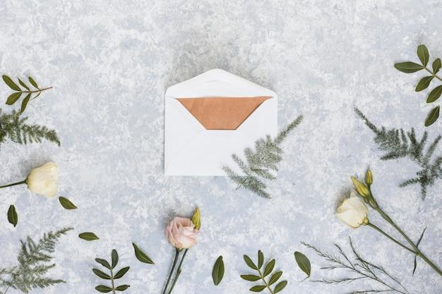 Umschlag mit rosen und pflanzenzweigen Kostenlose Fotos