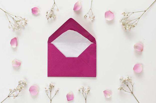 Umschlag zwischen frischen rosenblättern und pflanzenzweigen Kostenlose Fotos