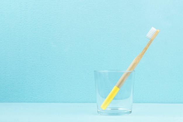 Umweltfreundliche bambuszahnbürste in einem transparenten glas auf einem blauen hintergrund mit kopienraum. null-abfall-konzept. Premium Fotos