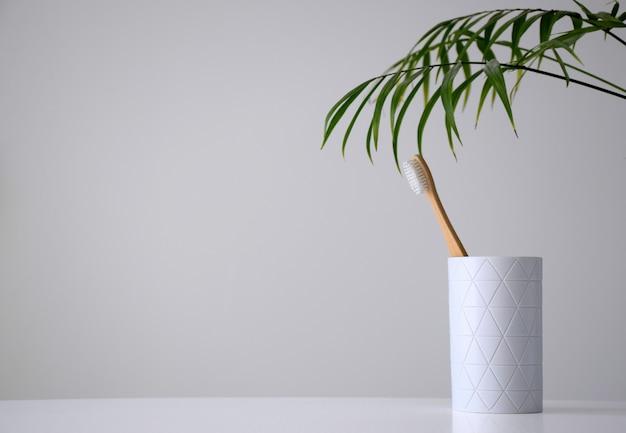 Umweltfreundliche bambuszahnbürste in weißem halter und palmblatt Premium Fotos