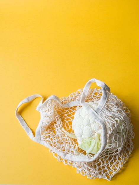 Umweltfreundliche beige einkaufstasche mit blumenkohl auf einem gelben hintergrund. Premium Fotos