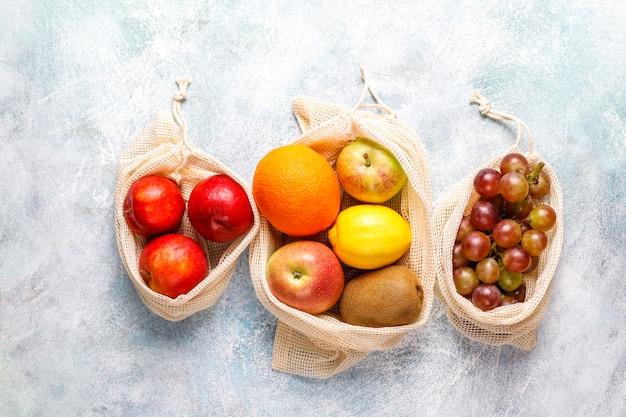 Umweltfreundliche, einfache einkaufstaschen aus beiger baumwolle zum kauf von obst und gemüse mit sommerfrüchten. Kostenlose Fotos