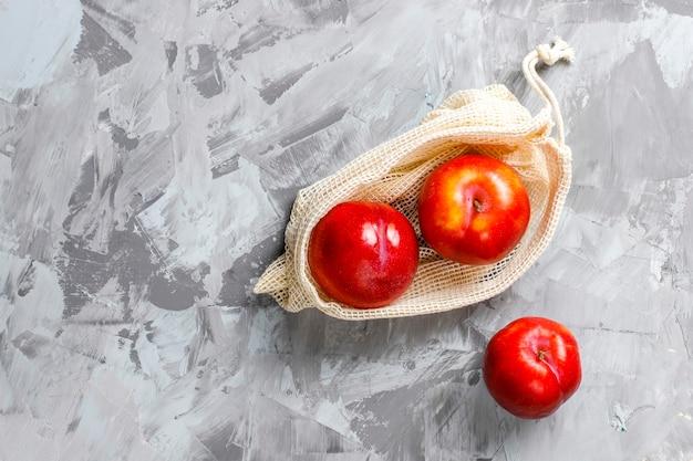 Umweltfreundliche einkaufstaschen aus einfacher beige baumwolle für den kauf von obst und gemüse mit sommerfrüchten. Kostenlose Fotos