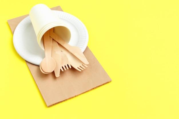Umweltfreundliche einwegutensilien aus bambusholz auf papiertüte in gelb Premium Fotos