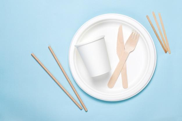 Umweltfreundliche einwegutensilien aus bambusholz und papier auf blauem grund. drapierte löffel, gabel, messer, bambusschalen mit pappbechern. Premium Fotos