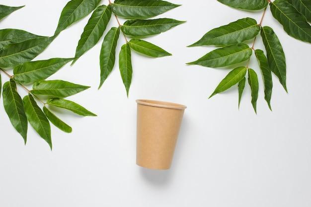 Umweltfreundliches stillleben. einweg-kaffeetasse aus pappkarton auf weißem hintergrund mit grünen tropischen blättern. gerichte mit natürlichen materialien Premium Fotos