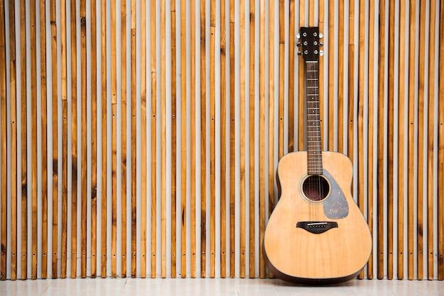 Unbedeutende akustikgitarre auf hölzernem hintergrund Kostenlose Fotos