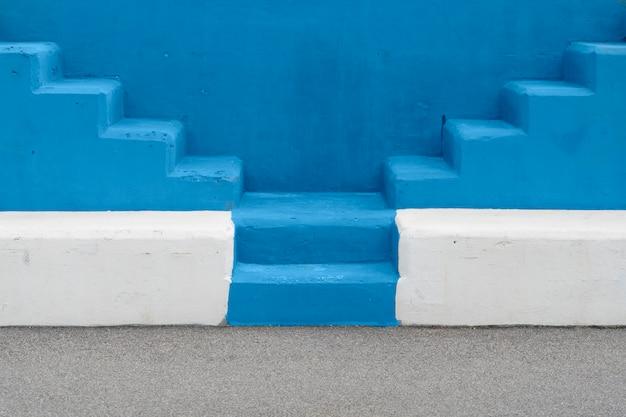 Unbedeutende hintergrundbeschaffenheitstreppe. modische farbe des jahres 2020. selektive ansicht des treppenhauses im freien mit blauem hintergrund. minimalistisches konzept. Premium Fotos