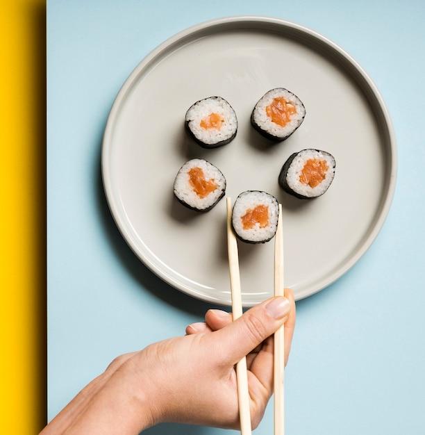 Unbedeutende platte mit sushirollen und essstäbchen Kostenlose Fotos