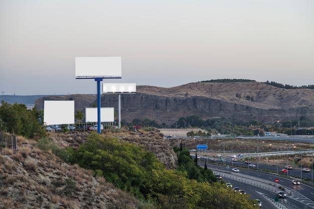 Unbelegte anschlagtafeln für neue reklameanzeige auf berg nahe der landstraße Kostenlose Fotos