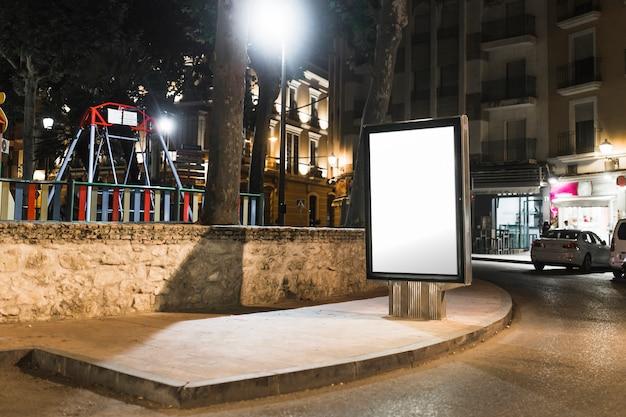 Unbelegte bushaltestelle, die anschlagtafel in der stadt nachts annonciert Kostenlose Fotos