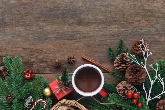 Unbelegte hölzerne planke verzieren mit kieferblatt, kieferkegeln, stechpalmekugeln, zuckerstange und roter schalenschokolade. Premium Fotos