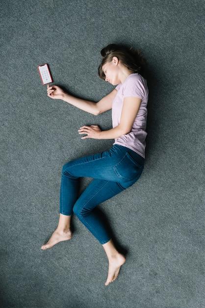 Unbewusste frau, die auf teppich nahe handy liegt Kostenlose Fotos