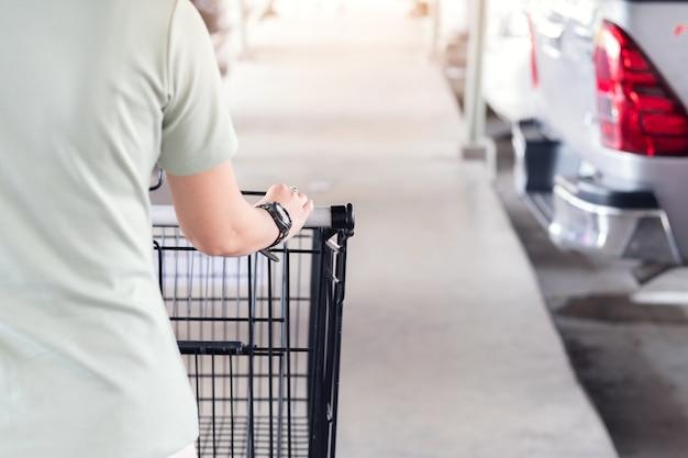 Undeutlich vom handfokus und von selektiven fokus des handfokus halten wagen arar carpark am supermarkt Premium Fotos