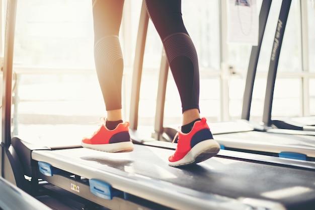Undeutlich von laufenden sportschuhen in der turnhalle, während eine junge frau joggen hat Premium Fotos