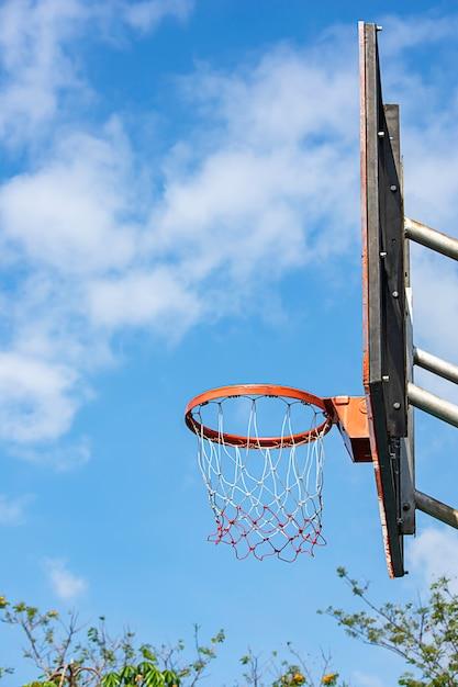 Undeutlicher baum des basketballkorbhintergrundes und der himmel. Premium Fotos