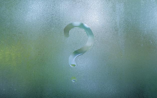 Undeutliches fragezeichen auf nebeligem kondensationsfensterglas Premium Fotos