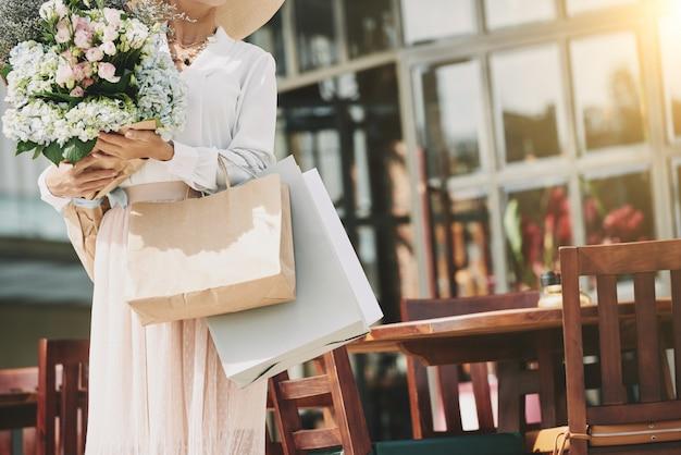 Unerkennbare elegante frau, die nahes straßencafé mit blumenblumenstrauß steht Kostenlose Fotos