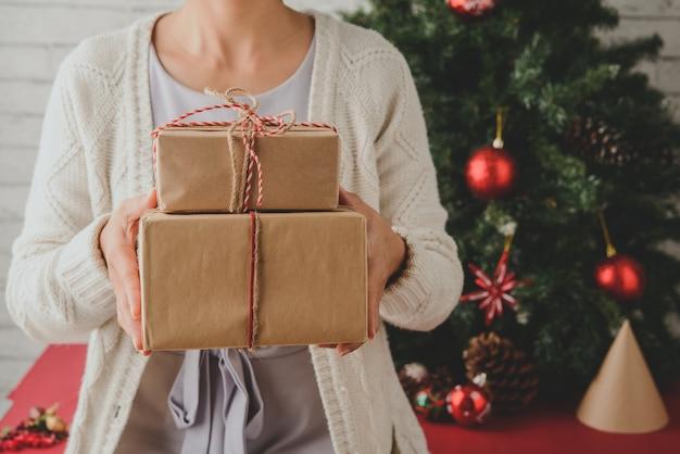 Unerkennbare frau, die zu hause eingewickelte geschenke vor weihnachtsbaum hält Kostenlose Fotos