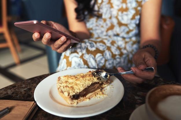 Unerkennbare junge frau, die im café sitzt, smartphone verwendet und streuseltorte isst Kostenlose Fotos