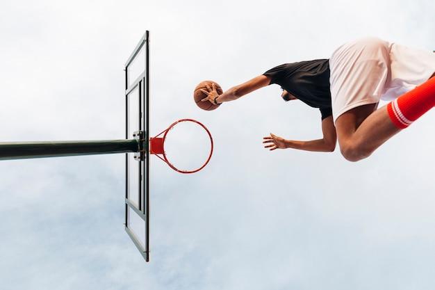 Unerkennbarer sportlicher mann, der basketball in netz wirft Kostenlose Fotos