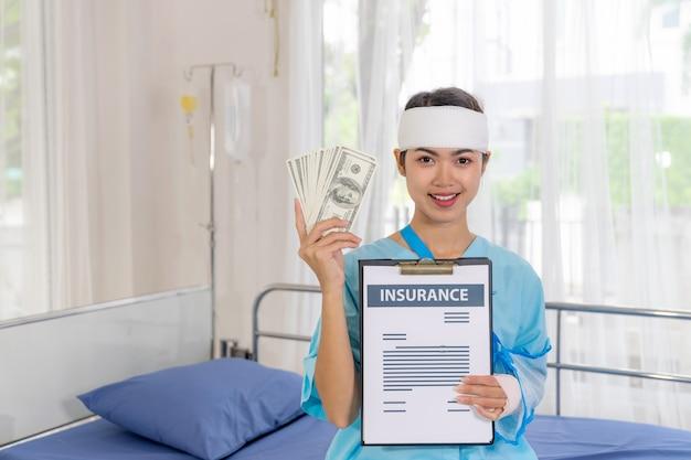 Unfallpatientin verletzungsfrau auf patientenbett im krankenhaus, die uns dollarnoten hält, freut sich über versicherungsgeld von versicherungsunternehmen - medizinisches konzept Kostenlose Fotos