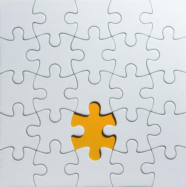 Unfertige weiße puzzlespielstücke auf orange hintergrund Premium Fotos