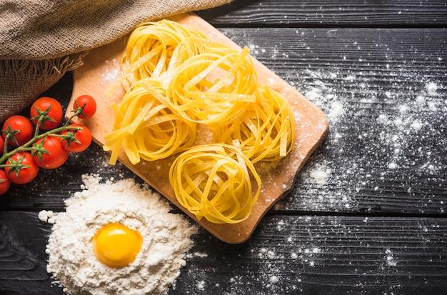 Ungekochte bandnudeln auf hackendem brett mit ei york im mehl und in den tomaten auf hölzerner planke Kostenlose Fotos