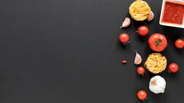 Ungekochte bandnudeln mit knoblauchzehen; tomate; und sauce auf schwarzem hintergrund Kostenlose Fotos